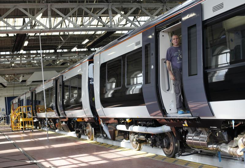 A worker stands in the doorway of a train at the Bombardier plant in Derby
