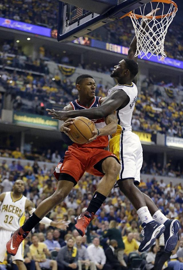 Washington Wizards' Bradley Beal, left, makes a pass against Indiana Pacers' Lance Stephenson during the first half of game 2 of the Eastern Conference semifinal NBA basketball playoff series Wednesday, May 7, 2014, in Indianapolis. (AP Photo/Darron Cummings)