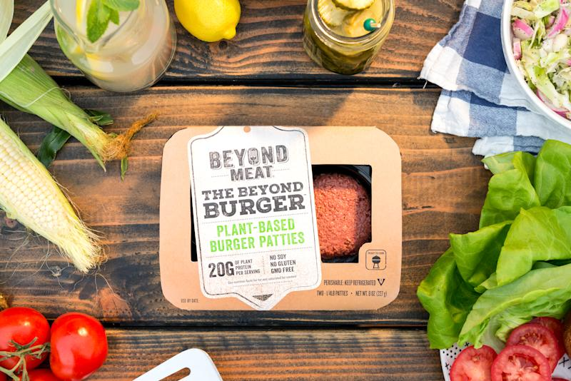 A package of Beyond Meat Burgers on a wooden table, surrounded by condiments and fixings