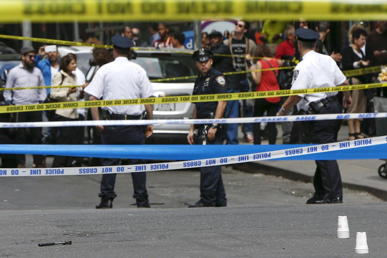 REFILE - ADDITIONAL CAPTION INFORMATION  Members of the NYPD police stand near the crime scene as a hammer (pictured left on the ground) lies on the ground, at the intersection of 37th street and 8th avenue in midtown Manhattan in New York, May 13, 2015.  A hammer-wielding man who hit three people on the head in tourist-packed areas of New York City earlier this week has been shot in a confrontation with police, New York media reported on Wednesday.   REUTERS/Shannon Stapleton