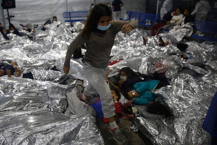A young female minor walks over others as they lie inside a pod for females at the Donna Department of Homeland Security holding facility, the main detention center for unaccompanied children in the Rio Grande Valley run by the US Customs and Border Protection, (CBP), in Donna, Texas on March 30, 2021. - The minors are housed by the hundreds in eight pods that are about 3,200 square feet in size. Many of the pods had more than 500 children in them. The Biden administration on Tuesday for the first time allowed journalists inside its main detention facility at the border for migrant children, revealing a severely overcrowded tent structure where more than 4,000 kids and families were crammed into pods and the youngest kept in a large play pen with mats on the floor for sleeping. (Photo by Dario Lopez-Mills / POOL / AFP)