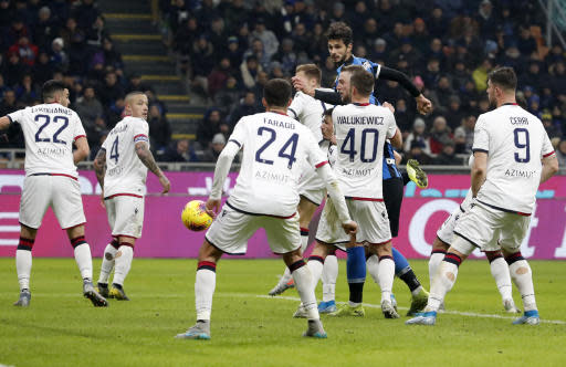 Inter Milan's Andrea Ranocchia, top, scores his side's fourth goal during an Italian Cup soccer match between Inter Milan and Cagliari at the San Siro stadium, in Milan, Italy, Tuesday, Jan. 14, 2020. (AP Photo/Antonio Calanni)