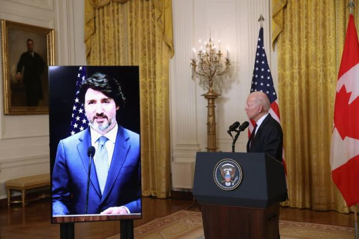 U.S. President Joe Biden looks on as Canada's Prime Minister Justin Trudeau, appearing via video conference call, gives closing remarks at the end of their virtual bilateral meeting from the White House in Washington