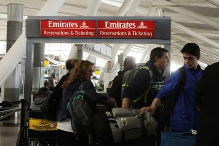 Travelers walk past an Emirates Airlines ticket desk at JFK International Airport in New York