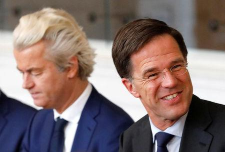 FILE PHOTO: Dutch Prime Minister Mark Rutte (R) of the VVD Liberal party and Dutch far-right politician Geert Wilders of the PVV Party take part in a meeting at the Dutch Parliament after the general election in The Hague, Netherlands, March 16, 2017.  REUTERS/Yves Herman/File Photo