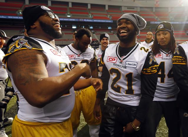 Hamilton Tiger-Cats Simoni Lawrence jokes around with Bryan Hall during their team's practice at the CFL's 102nd Grey Cup week in Vancouver, British Columbia November 29, 2014. The Hamilton Tiger Cats will play the Calgary Stampeders for the Canadian Football League championship title at B.C. Place on Sunday in Vancouver. REUTERS/Mark Blinch (CANADA - Tags: SPORT FOOTBALL)