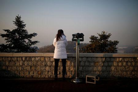 A woman next to a pair of binoculars looks toward the north near the militarized zone separating the two Koreas, in Paju, South Korea, December 21, 2017. REUTERS/Kim Hong-Ji