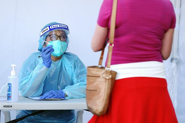 A healthcare worker wearing personal protective equipment (PPE) speaks to a person at the St Vincent's Hospital Coviv-19 Screening Clinic in the Rushcutters Bay suburb of Sydney, Australia.