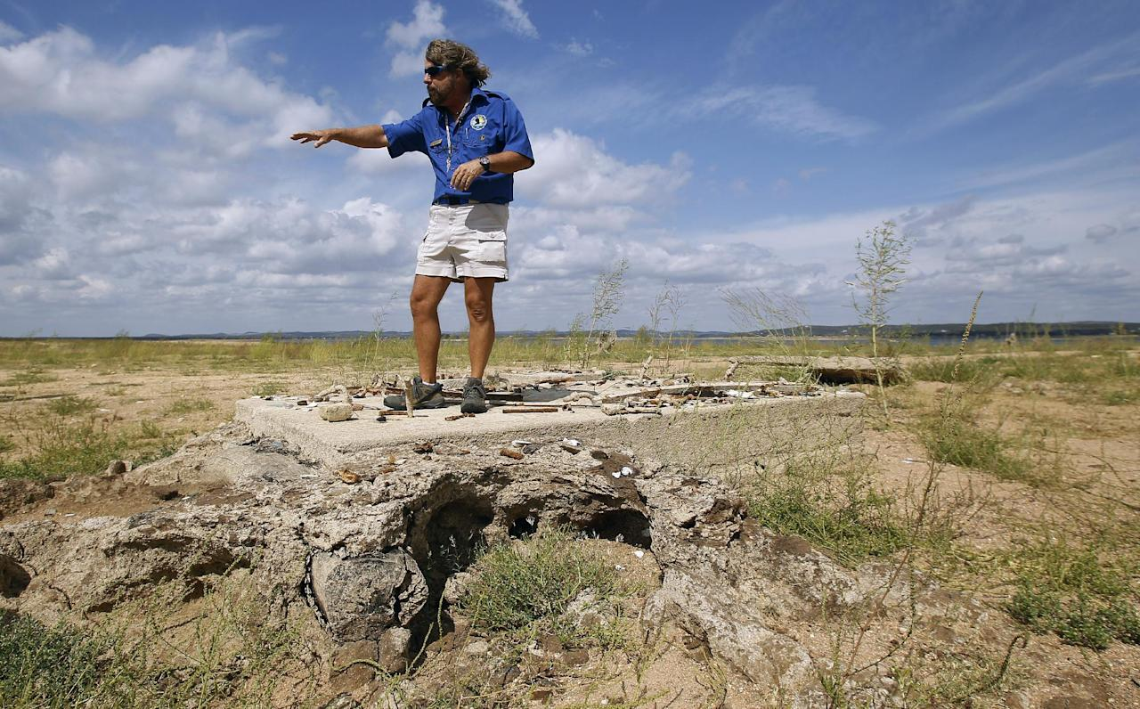 In this Oct. 5, 2011 photo, tour guide Tim Mohan stands on the concrete foundation of an old cotton gin in the old town of Bluffton, Texas. The gin resurfaced on the now dry, sandy lake near Bluffton, as the Texas drought shrinks the state's largest inland lake. (AP Photo/Eric Gay)