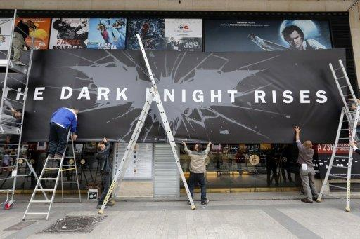 Employees remove promotional boards  where the French premiere of the Batman movie was supposed to take place