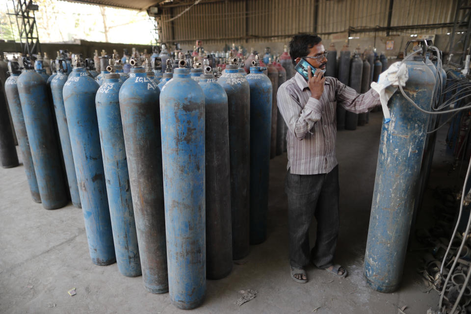 A worker refills medical oxygen cylinders at a charging station on the outskirts of Prayagraj, India, Friday, April 23, 2021. India put oxygen tankers on special express trains as major hospitals in New Delhi on Friday begged on social media for more supplies to save COVID-19 patients who are struggling to breathe. India's underfunded health system is tattering as the world's worst coronavirus surge wears out the nation, which set another global record in daily infections for a second straight day with 332,730. (AP Photo/Rajesh Kumar Singh)
