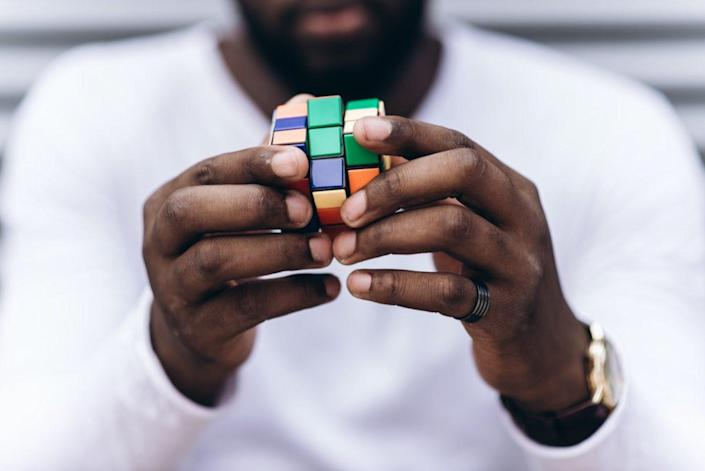 man wearing casual clothes collect Rubik's Cube