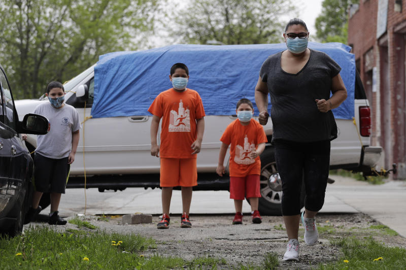 Mariana Ochoa, right, runs as her children watch her in front of her home in Chicago, Friday, May 22, 2020. Chicago Run's at-home fitness programs have become an essential part of the Ochoa family's routine during the coronavirus pandemic. (AP Photo/Nam Y. Huh)