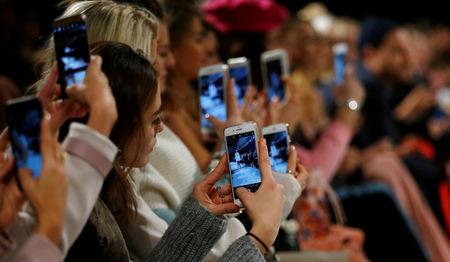 FILE PHOTO: A so-called media influencer takes pictures at Berlin Fashion Week, January 19, 2017. REUTERS/Hannibal Hanschke/File Photo