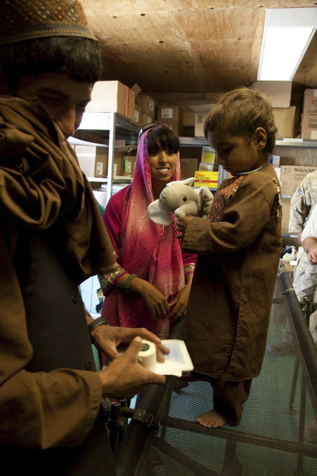 In this image released by the Defense Department, a member of the U.S. Army Cultural Support Team, attached to Special Operations Task Force - South, gives a stuffed animal to a local boy after treating his burn wound on a remote operating base in northern Khakrez District, on July 3, 2011, in Kandahar province, Afghanistan. (AP Photo/U.S. Army, Pfc. Kaimana-Ipulani Kalauli-Mendoza)