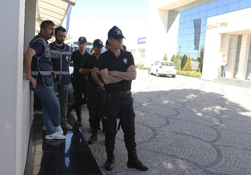 Turkish police officers stand next to the Koza Ipek Holding building in Ankara on September 1, 2015, after a major swoop of the media group critical of Erdogan and tied to his political nemesis, Muslim cleric Fethullah Gulen