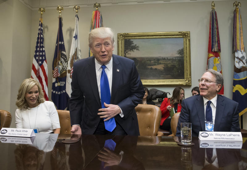 President Donald Trump takesa seat between White and National Rifle Associationleader Wayne LaPierre at a White House meeting on Feb. 1, 2017. (Pool via Getty Images)