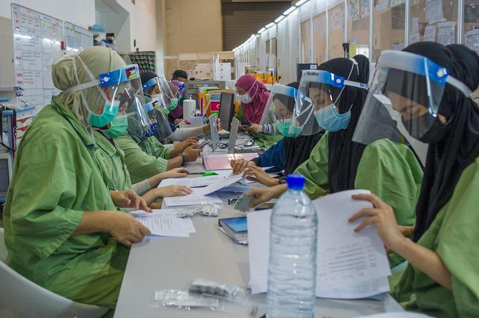 Health workers are pictured at the Covid-19 Low-Risk Quarantine and Treatment Centre at the Malaysia Agriculture Expo Park in Serdang May 19, 2021. — Picture by Shafwan Zaidon