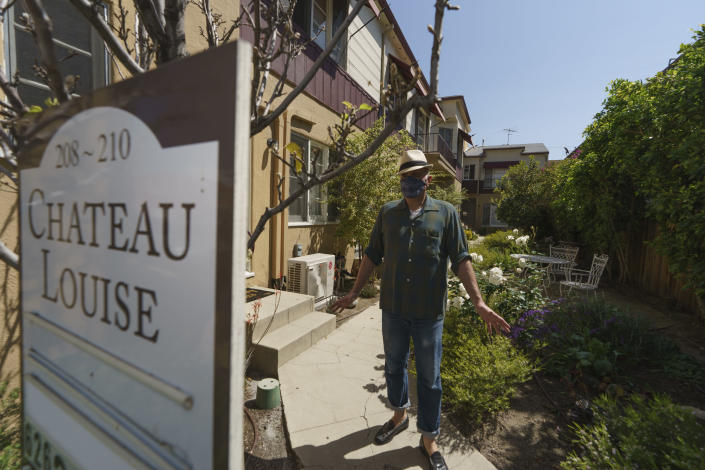 Nathan Long, a video game writer, walks outside his rental apartment communal garden in Glendale, Calif., Thursday, April 8, 2021. He and his wife, Lili, have been unsuccessful so far in their search for a home in Los Angeles. (AP Photo/Damian Dovarganes)