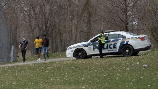 A Gatineau Police Service officer stands watch at Parc des Cèdres in the city's Aylmer district as three men walk by on April 11, 2021.