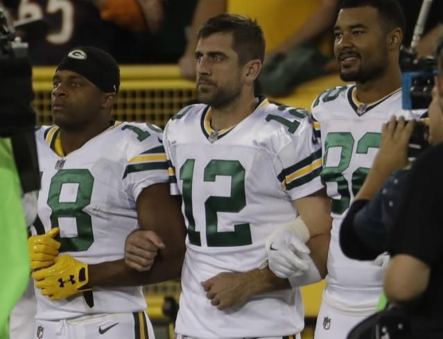 "Green Bay Packers' Aaron Rodgers links arms with Richard Rodgers and <a class=""link rapid-noclick-resp"" href=""/nfl/players/24851/"" data-ylk=""slk:Randall Cobb"">Randall Cobb</a> during the national anthem before a game against the Chicago Bears on Sept. 28, 2017. (AP Photo/Morry Gash)"