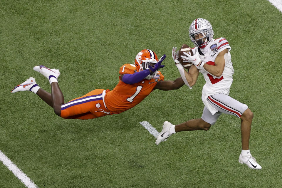 FILE - Ohio State wide receiver Chris Olave catches a touchdown pass in front of Clemson cornerback Derion Kendrick during the second half of the Sugar Bowl NCAA college football game in New Orleans, in this Friday, Jan. 1, 2021, file photo. Olave was selected to The Associated Press Preseason All-America first team offense, Monday Aug. 23, 2021. (AP Photo/Butch Dill, File)