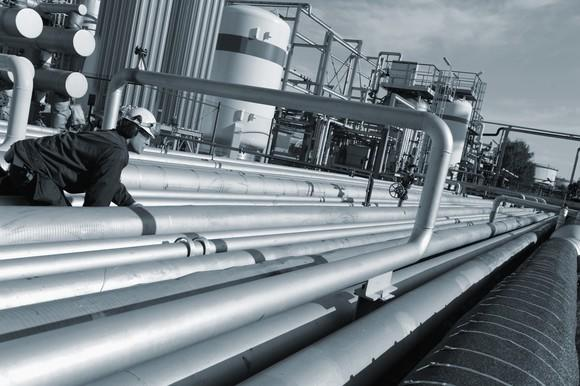 Worker inspecting oil pipelines.