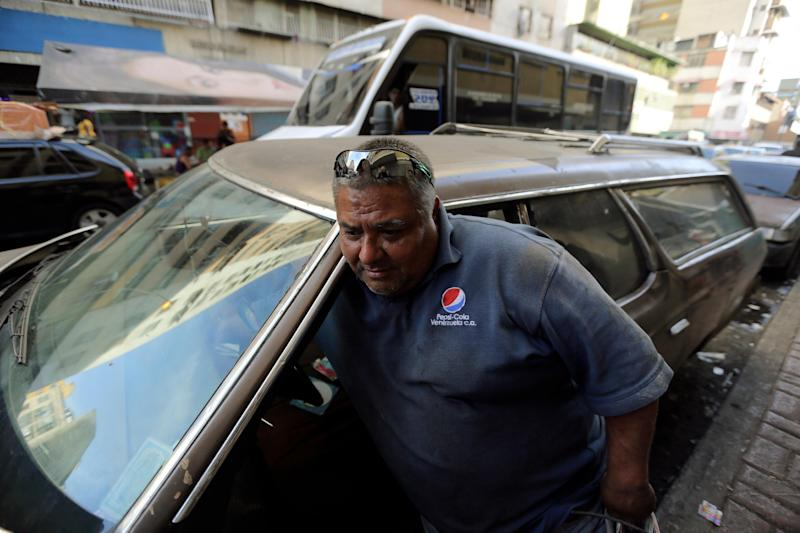 In this Thursday, Dec. 19, 2013 photo, Ruben Ruiz emerges from his 1975 Ford LTD station wagon in Caracas, Venezuela. The loud, steady roar of Nixon-era gas guzzlers is sounding a little less muscular these days on the smog-filled streets of Caracas. As a grueling economic crisis drains the government's coffers, President Nicolas Maduro is putting motorists on notice and taking on one of the nation's biggest political taboos: the cheap price of gas. (AP Photo/Fernando Llano)