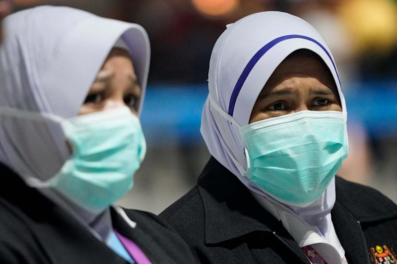 Health officials wear face masks at an inspection site at the Kuala Lumpur International Airport in Sepang: AP