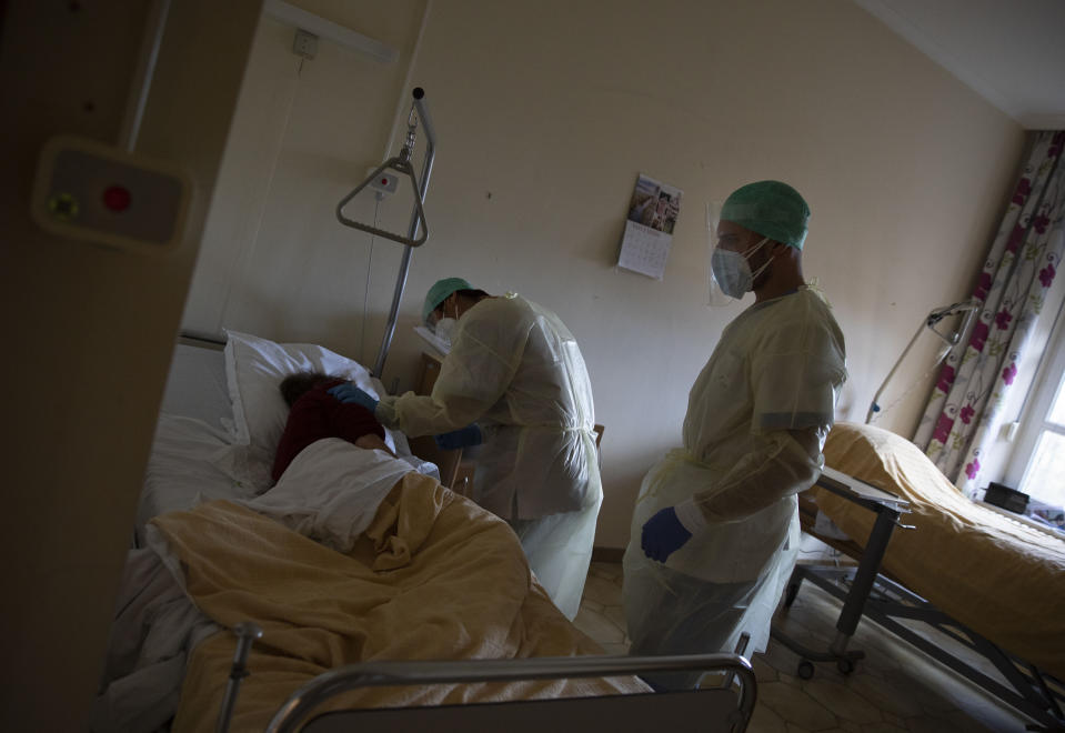 A supervisor, left, and a healthcare worker help a patient suffering from coronavirus to feel more comfortable as they do their rounds in the COVID-19 ward of the CHC nursing home in Landenne, Belgium, Wednesday, Nov. 4, 2020. Belgium, proportionally still the worst-hit nation in Europe when it comes to coronavirus cases, said Wednesday that there were increasing signs of that a turning point in the crisis was drawing close. The Belgian Army has been deployed to help several hard hit areas in the country including nursing homes. (AP Photo/Virginia Mayo)