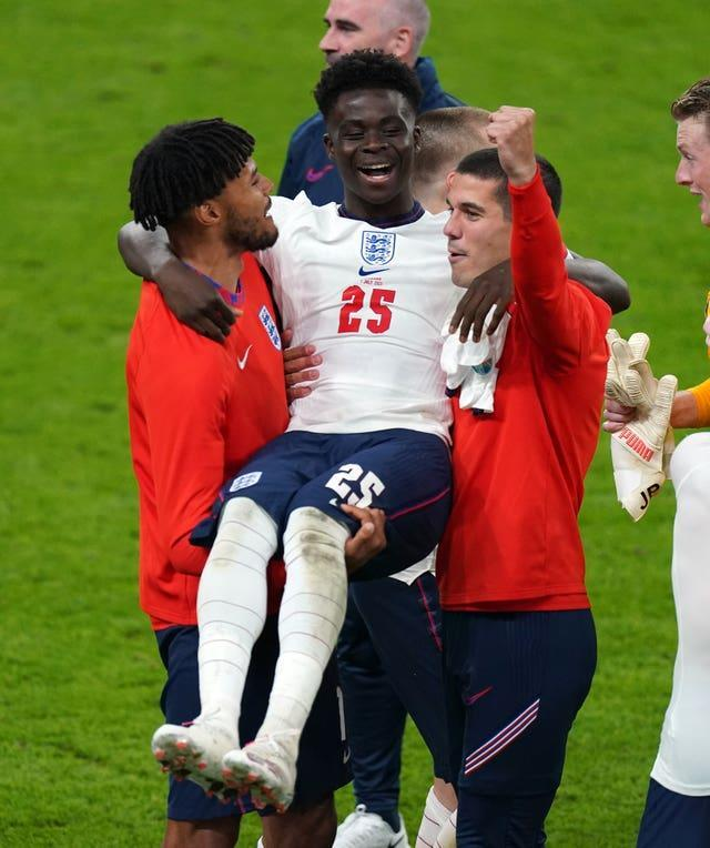 Tyrone Mings and Conor Coady carry Bukayo Saka as they celebrate victory over Denmark