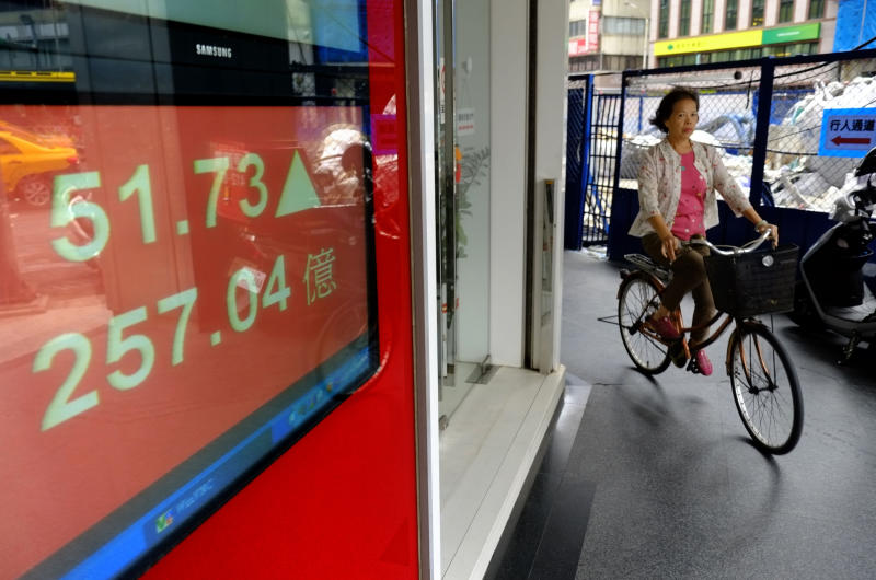 A woman rides past a brokerage displaying Taiwan's stock market up on opening in Taipei, Taiwan, Thursday, Oct. 17, 2013. An eleventh hour agreement that averted a U.S. government debt default boosted Asian stock markets Thursday. (AP Photo/Wally Santana)