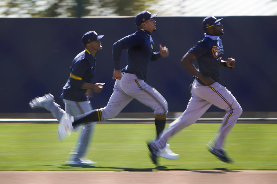 Milwaukee Brewers players, from left Corey Ray, Avisail Garcia and Lorenzo Cain runs across the field during the team's spring training baseball workout in Phoenix , Tuesday, Feb. 23, 2021. (AP Photo/Jae C. Hong)