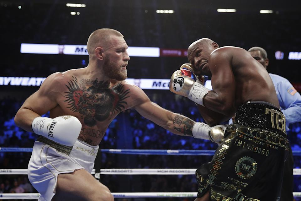 Conor McGregor, left, fights Floyd Mayweather Jr. in a super welterweight boxing match Saturday, Aug. 26, 2017, in Las Vegas. (AP Photo/Isaac Brekken)