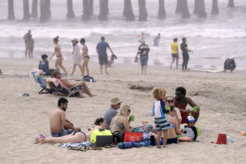 FILE - In this April 26, 2020, file photo, people sit on the beach in Huntington Beach, Calif. A memo sent to California police chiefs says Gov. Gavin Newsom will order all beaches and state parks closed starting Friday, May 1, to curb the spread of the coronavirus. The California Police Chiefs Association sent the bulletin to its members Wednesday evening. Association President Eric Nuñez said it was sent to give chiefs time to plan ahead of Newsom's expected announcement Thursday. (AP Photo/Marcio Jose Sanchez, File)