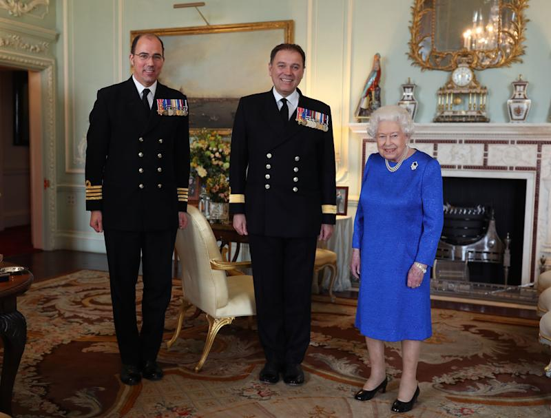 LONDON, ENGLAND - MARCH 18: Queen Elizabeth II receives Commodore Steven Moorhouse (centre, outgoing Commanding Officer, HMS Queen Elizabeth) and Captain Angus Essenhigh (incoming Commanding Officer), during a private audience in the Queens Private Audience Room in Buckingham Palace on March 18, 2020 in London, England. (Photo by Yui Mok - WPA Pool/Getty Images)