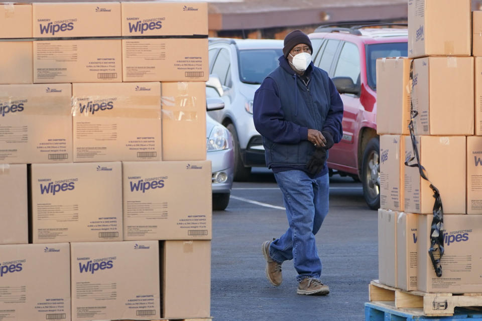 A man walks past pallets of disinfecting wipes as he arrives at Ebenezer Baptist Church for a COVID-19 vaccine, Jan. 26, 2021, in Oklahoma City. Rev. Derrick Scobey, Ebenezer Baptist Church Senior Pastor helped to organize the event in an effort to encourage more African Americans in Oklahoma City to receive the vaccine. (AP Photo/Sue Ogrocki)