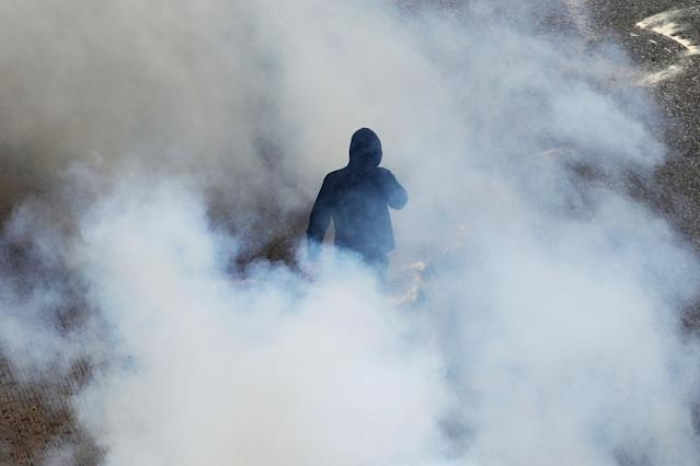 <p>A protester walks among smoke from a tear gas thrown by riot police during clashes at a nationwide general strike demonstration, in Athens Wednesday, May 17, 2017. Greek workers walked off the job across the country Wednesday for an anti-austerity general strike that was disrupting public and private sector services across the country. (AP Photo/Petros Giannakouris) </p>