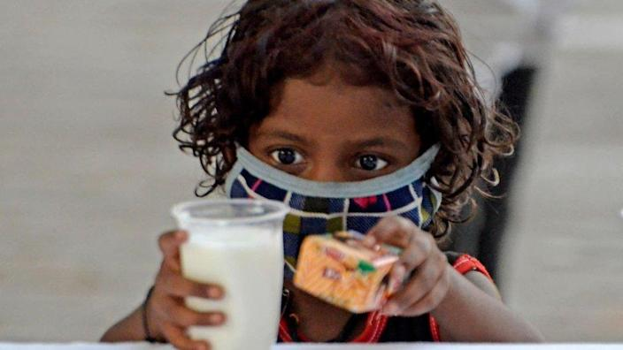 A poor child takes a glass of milk and a packet of biscuits during a free glass of milk and biscuit packet distribution organised by Kolkata police amid coronavirus emergency in Kolkata, India, 23 May, 2021. In
