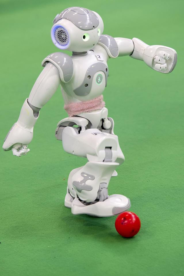 MAGDEBURG, GERMANY - APRIL 26: Two teams of robots play against each other in soccer at the 2013 RoboCup German Open tournament on April 26, 2013 in Magdeburg, Germany. The robots, which are a model called Nao, manufactured by Aldebaran Robotics, perform autonomously and communicate with one another via WLAN. The three-day tournament is hosting 43 international teams and 158 German junior teams that compete in a variety of disciplines, including soccer, rescue and dance. (Photo by Jens Schlueter/Getty Images)