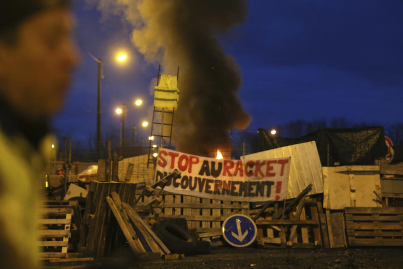 "A demonstrator stands in front of a makeshift barricade set up by the so-called yellow jackets to block the entrance of a fuel depot in Le Mans, western France, Tuesday, Dec. 5, 2018, with banner reading ""Stop the Government racket"". French government's decision to suspend fuel tax and utility hikes Tuesday did little to appease protesters, who called the move a ""first step"" and vowed to fight on after large-scale rioting in Paris last weekend. (AP Photo/David Vincent)"