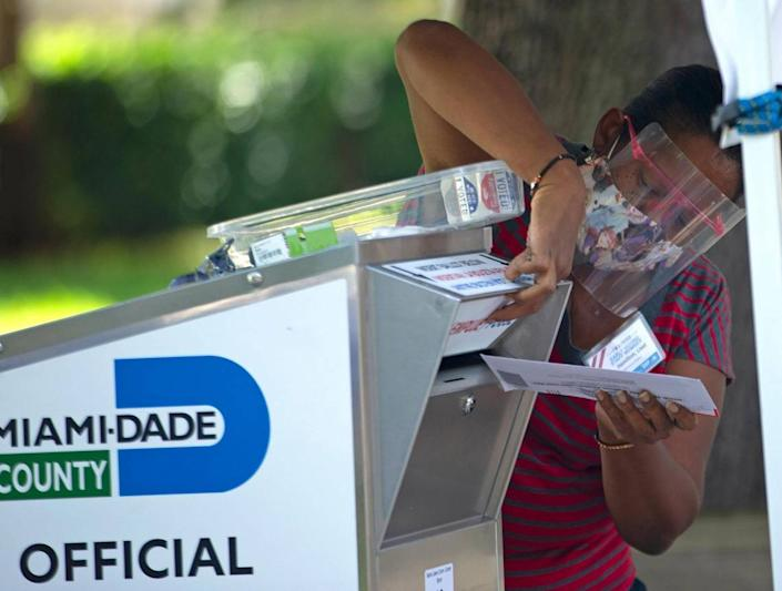 A poll worker deposits a ballot after collecting from a citizen during the early voting for primary election at Miami Lakes Community Center located at 15151 Montrose Rd. in Hialeah on Thursday, August 13, 2020.