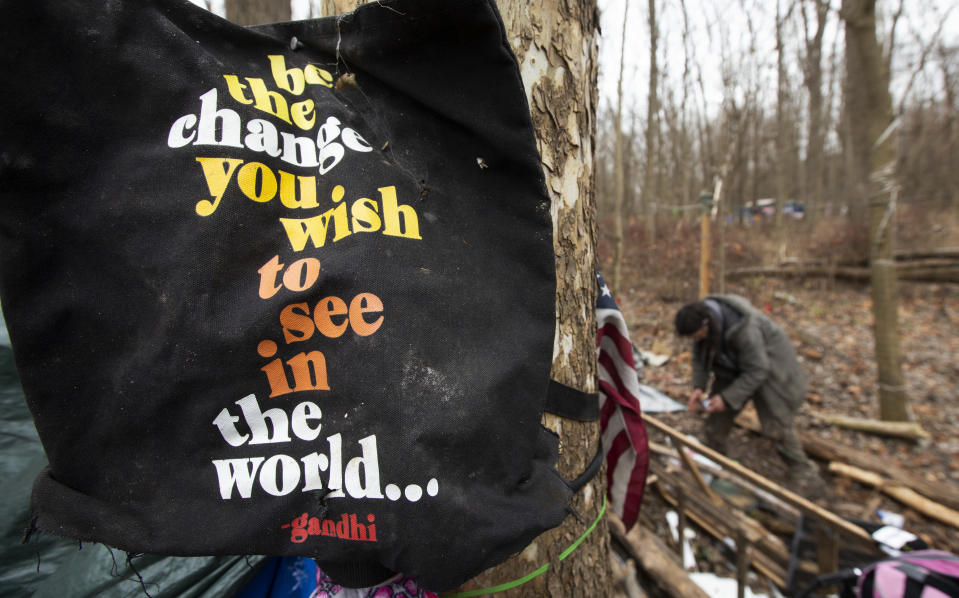 Jose Ortiz organizes some of his belongings at the residence he built in the homeless encampment known as the Jungle on Monday, Dec. 7, 2020, in Ithaca, N.Y. The pandemic has caught homeless service providers in a crosscurrent: demand is high, but their ability to provide services are constricted. (AP Photo/John Munson)