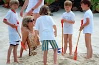 <p>Looking chic in a leopard print bathing suit, Diana has some fun in the sand with her adorable sons, Prince William and Prince Harry, during a vacation on Necker Island in April 1990. </p>