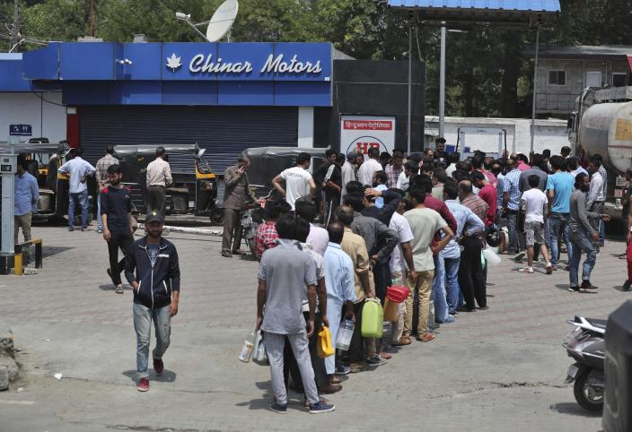 Kashmiri residents queue up at a fuel station in Srinagar, India, Sunday, Aug. 4, 2019. People in Srinagar and other towns in Indian kashmir thronged grocery stores and medical shops to stock up on essentials. Tensions have soared along the volatile, highly militarized frontier between India and Pakistan in the disputed Himalayan region of Kashmir as India deployed more troops and ordered thousands of visitors out of the region. (AP Photo/Mukhtar Khan)