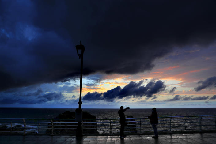 Storm clouds move in at sunset as people take pictures, in Beirut, Lebanon, Tuesday, Feb. 16, 2021. (AP Photo/Hussein Malla)