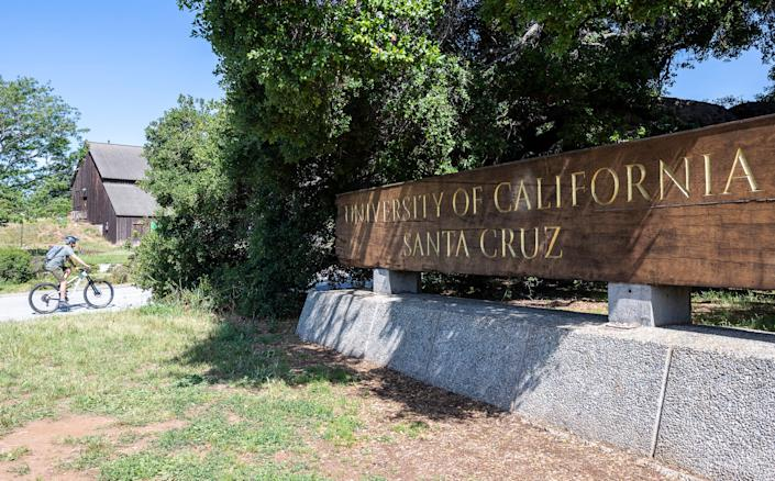 A bicyclist rides near the wooden University of California Santa Cruz sign in Santa Cruz, Calif, on Friday, May 22, 2020.