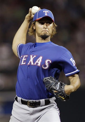 Texas Rangers starting pitcher Yu Darvish throws to the Colorado Rockies during the third inning of a spring training baseball game on Friday, March 30, 2012, in Scottsdale, Ariz. (AP Photo/Marcio Jose Sanchez)