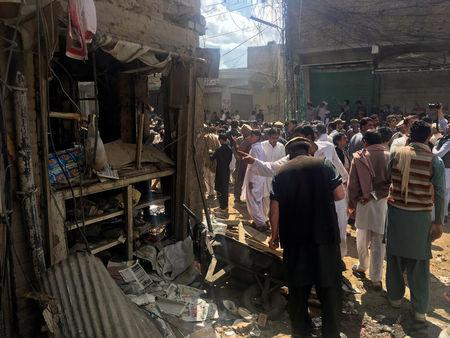 Residents gather near a damaged shop in a market after a blast in Parachinar, Pakistan