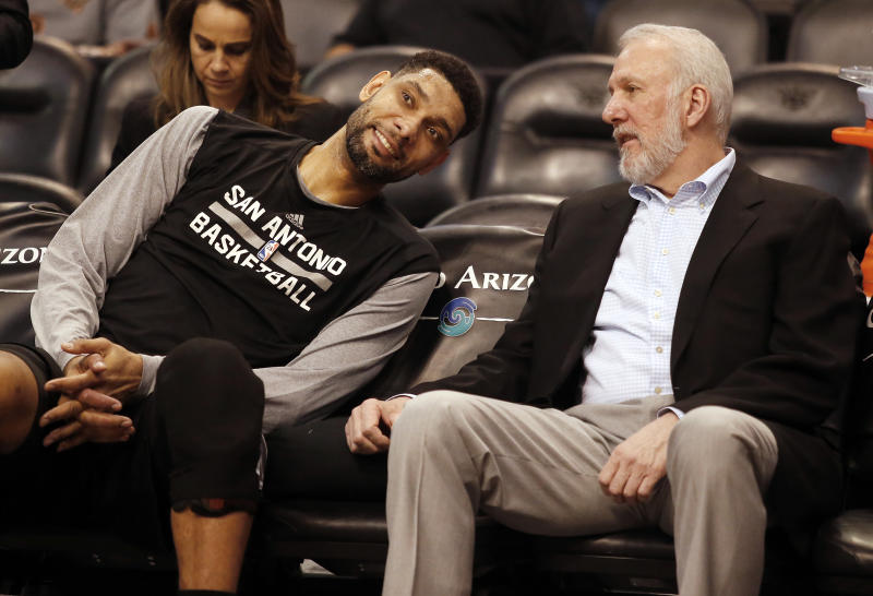 FILE - In this Feb. 28, 2015, file photo, San Antonio Spurs forward Tim Duncan, left, and head coach Gregg Popovich chat on the bench during the first quarter of an NBA basketball game against the Phoenix Suns in Phoenix. They were joined at the hip for 19 years, a player and coach combination that enjoyed more wins than any in NBA history. And now that Duncan's playing days are done, Popovich is about to start anew in some respects. (AP Photo/Rick Scuteri, File)